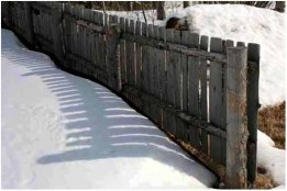Shadowed fence in snow